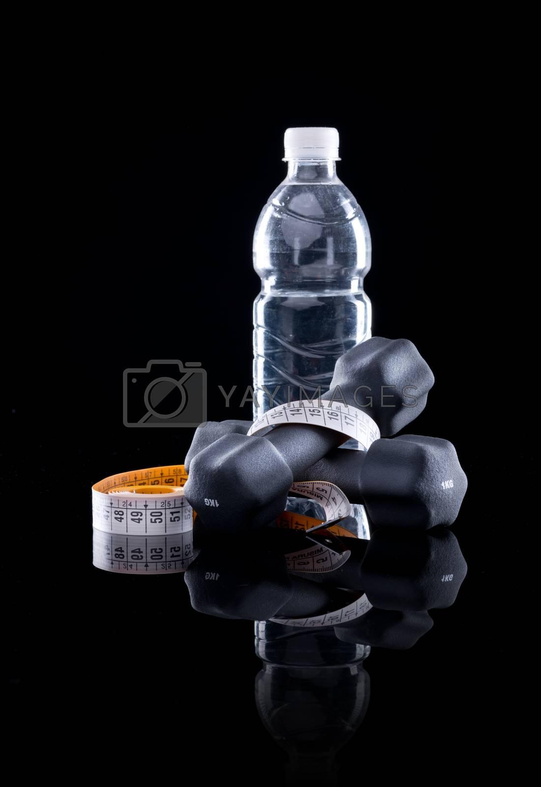 Water bottle, measure tape and dumbbells on black background.
