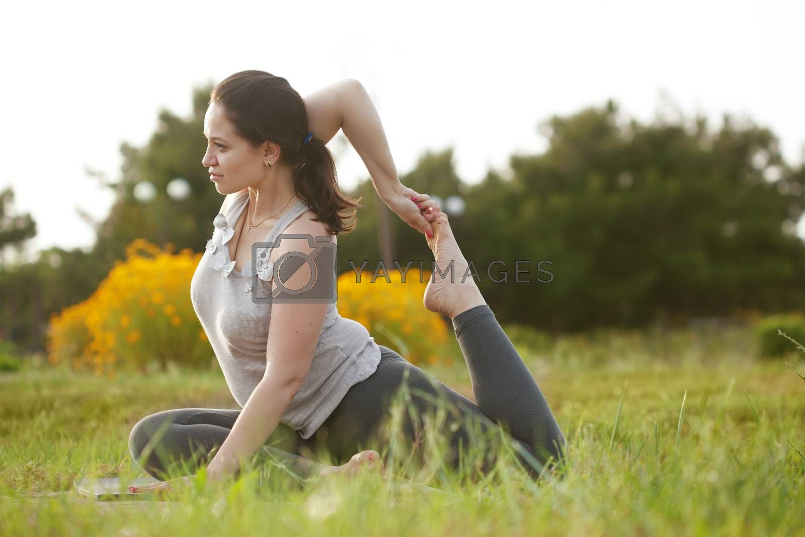 Young woman doing yoga exercise outdoors