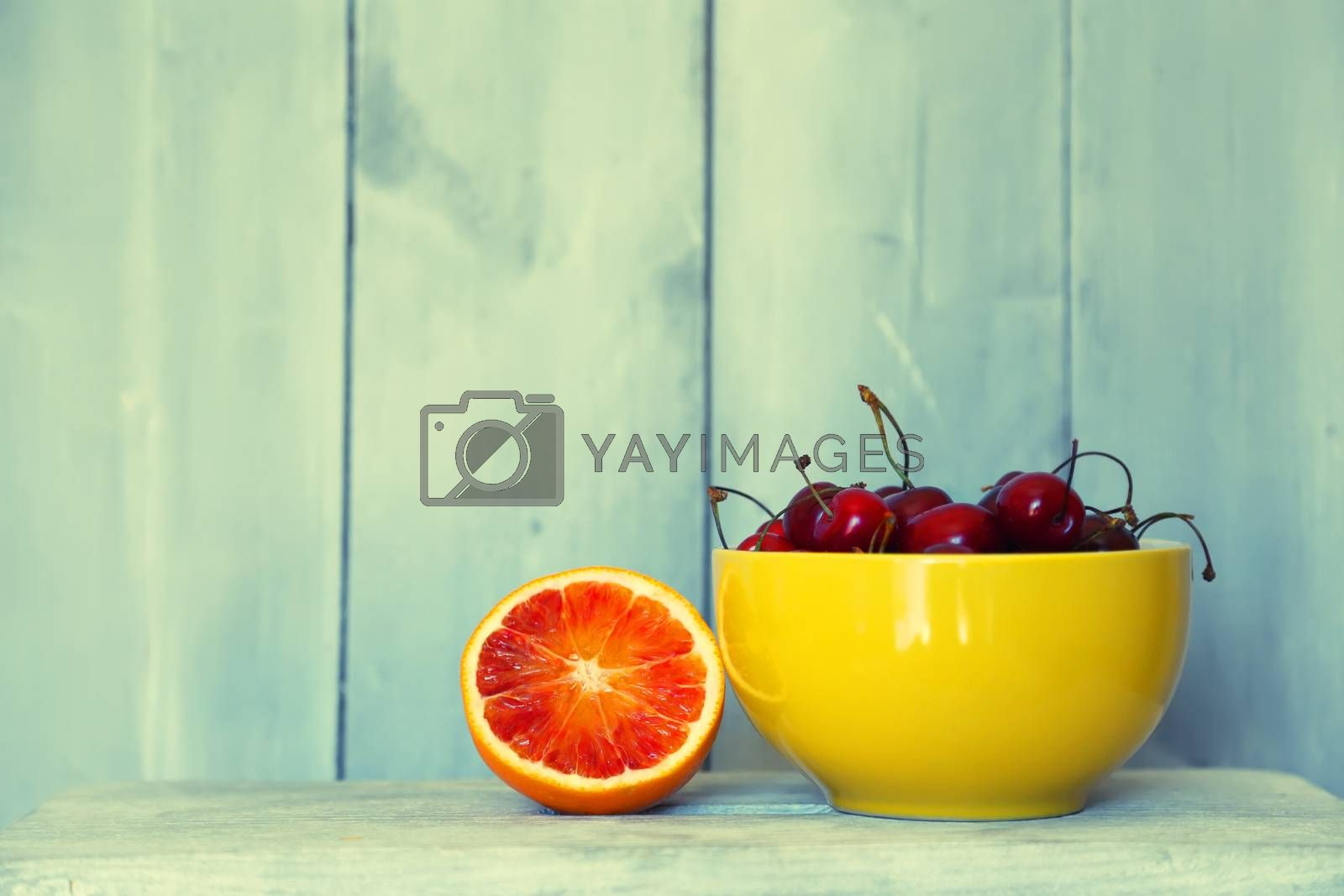 Photo of ripe cherries on wooden background