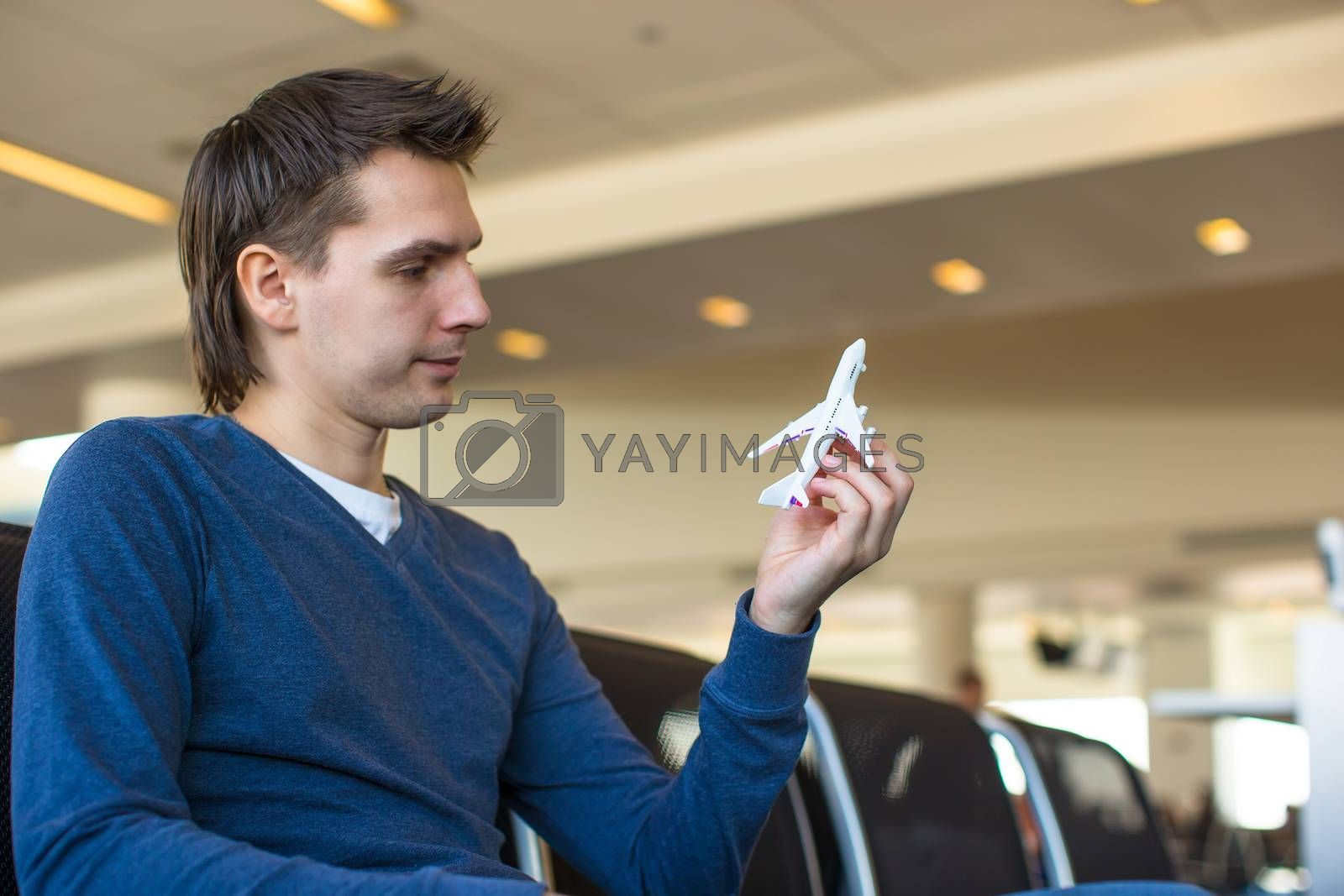 Young man with a small model airplane inside a large aircraft