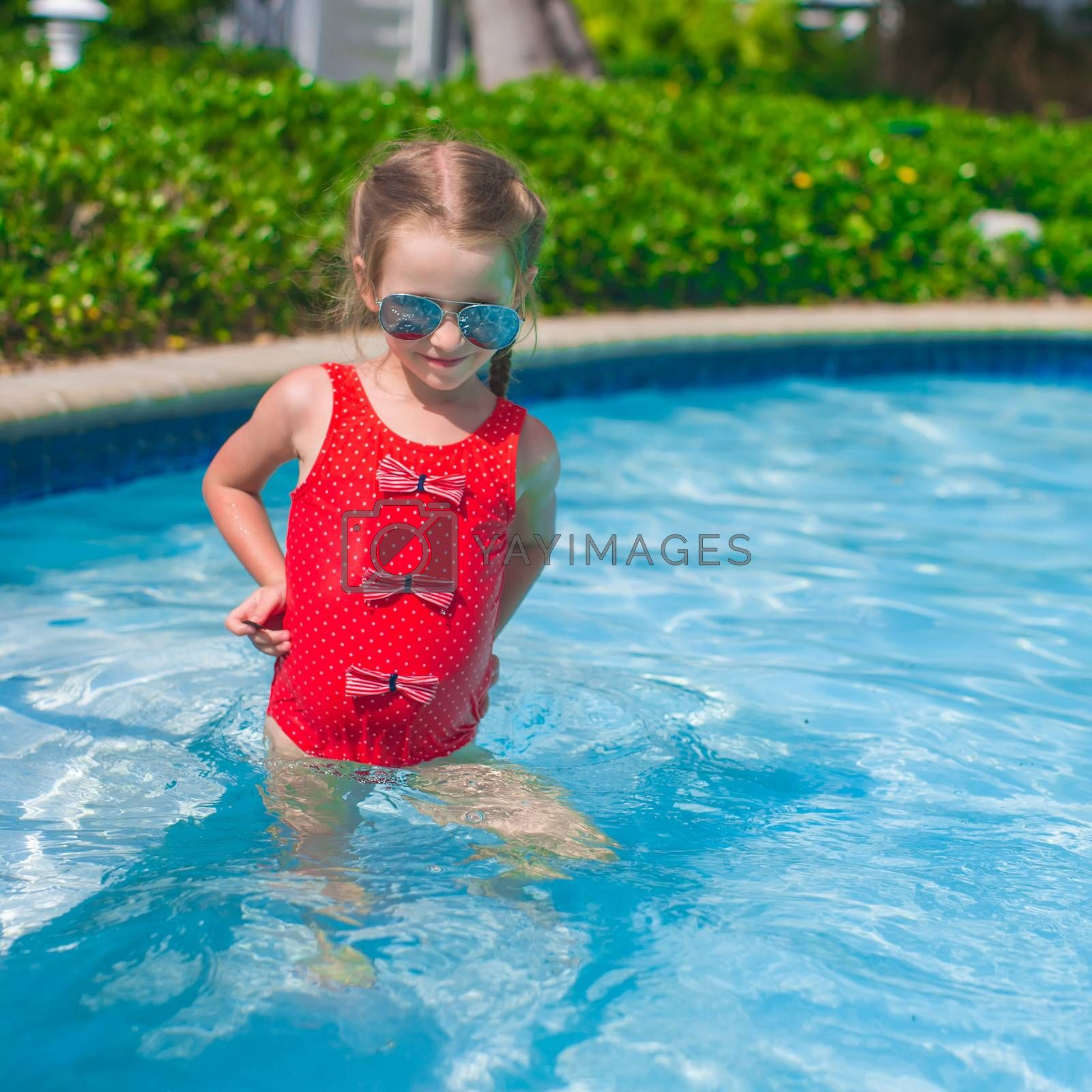 Little happy girl swims in the swimming pool
