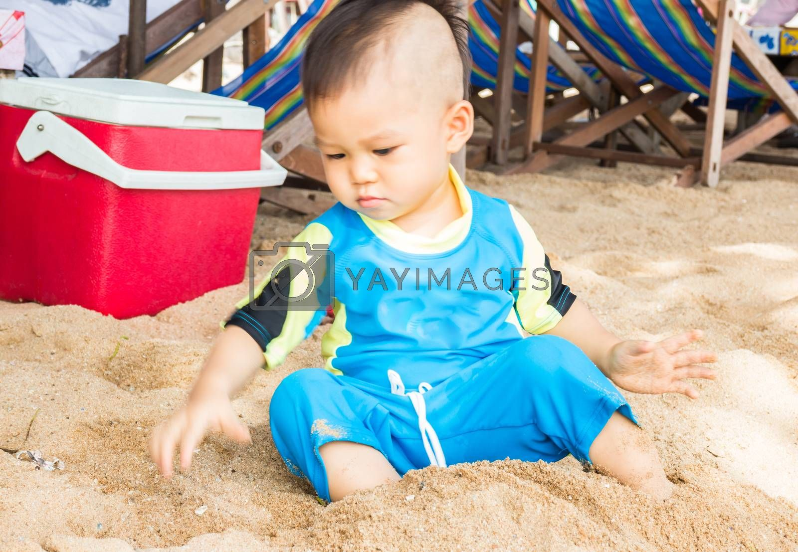 Little asian boy playing sand on the beach, stock photo