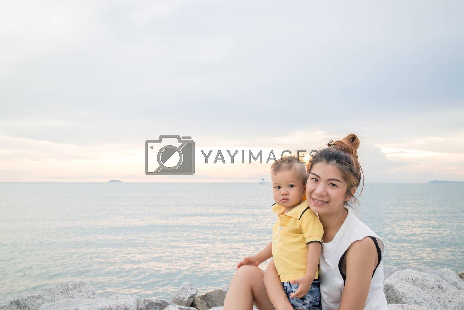Asian boy pose on the beach with his mother, stock photo