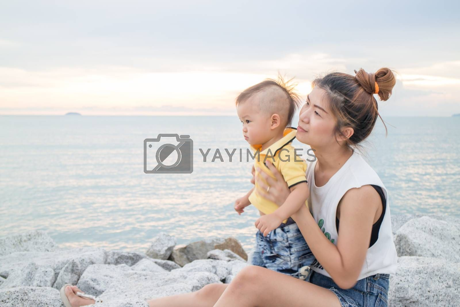 Asian boy chilling on the beach with his mother, stock photo