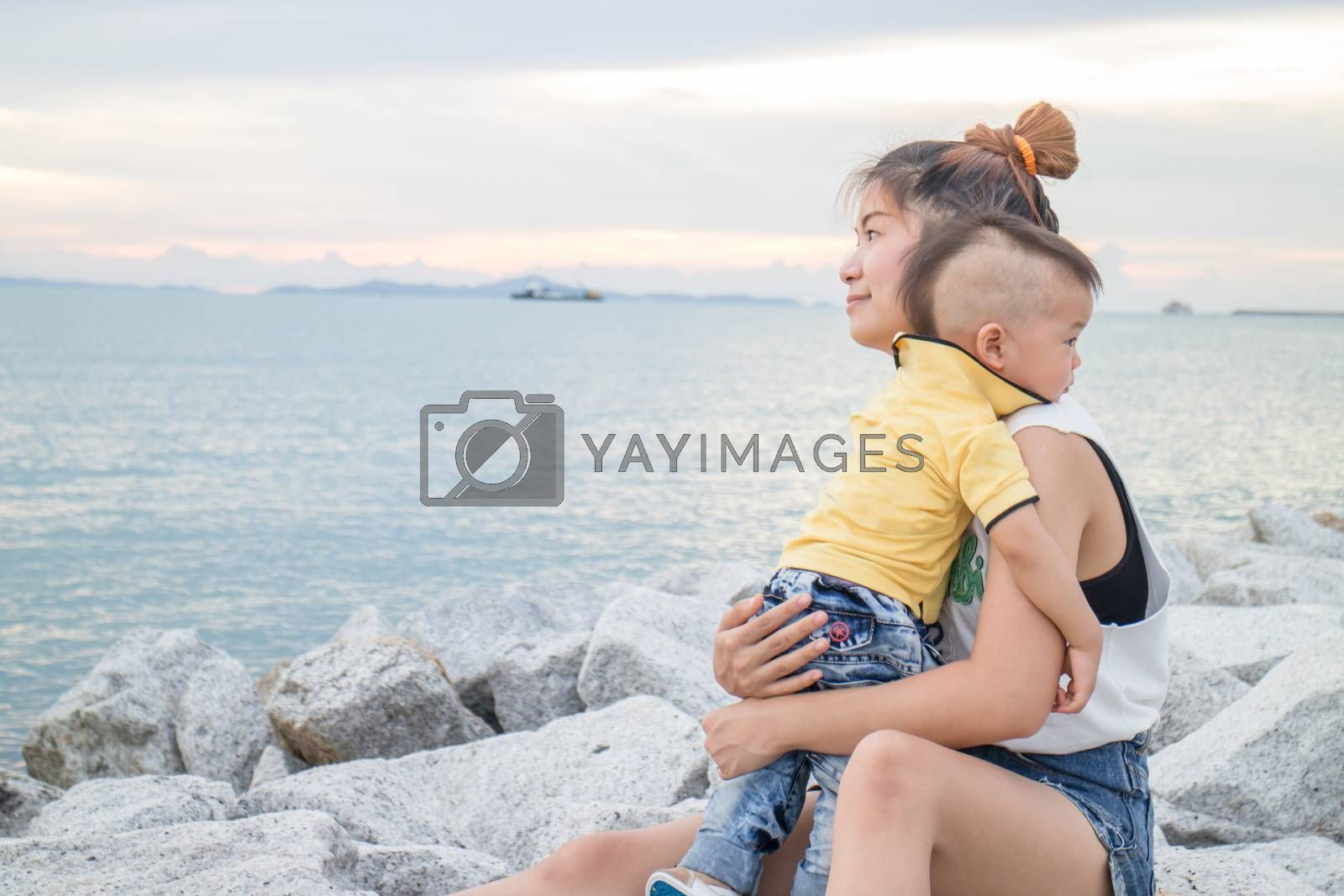 Asian boy chilling with his mother on seaside, stock photo
