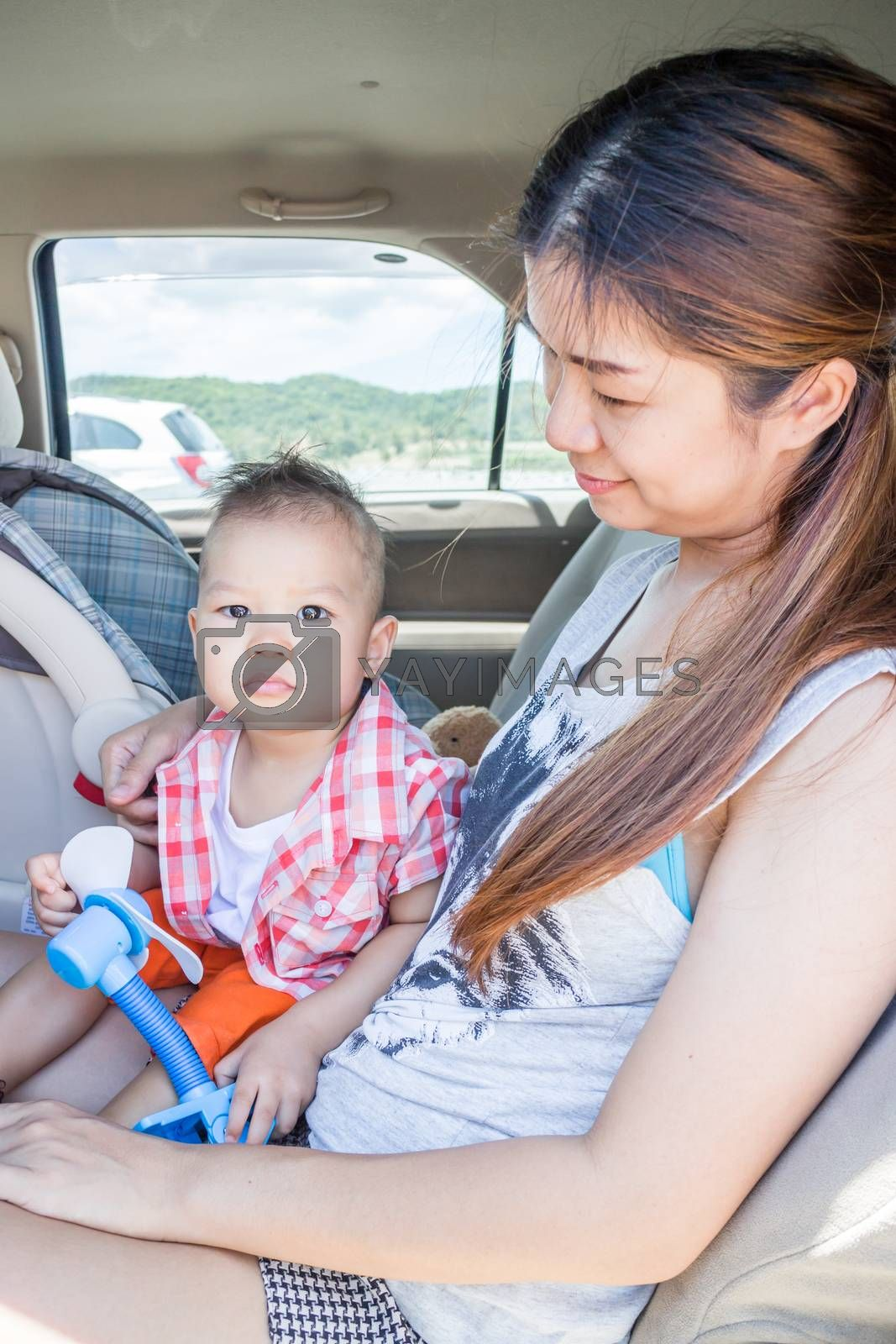 Cute boy sitting in the car with his mother, stock photo