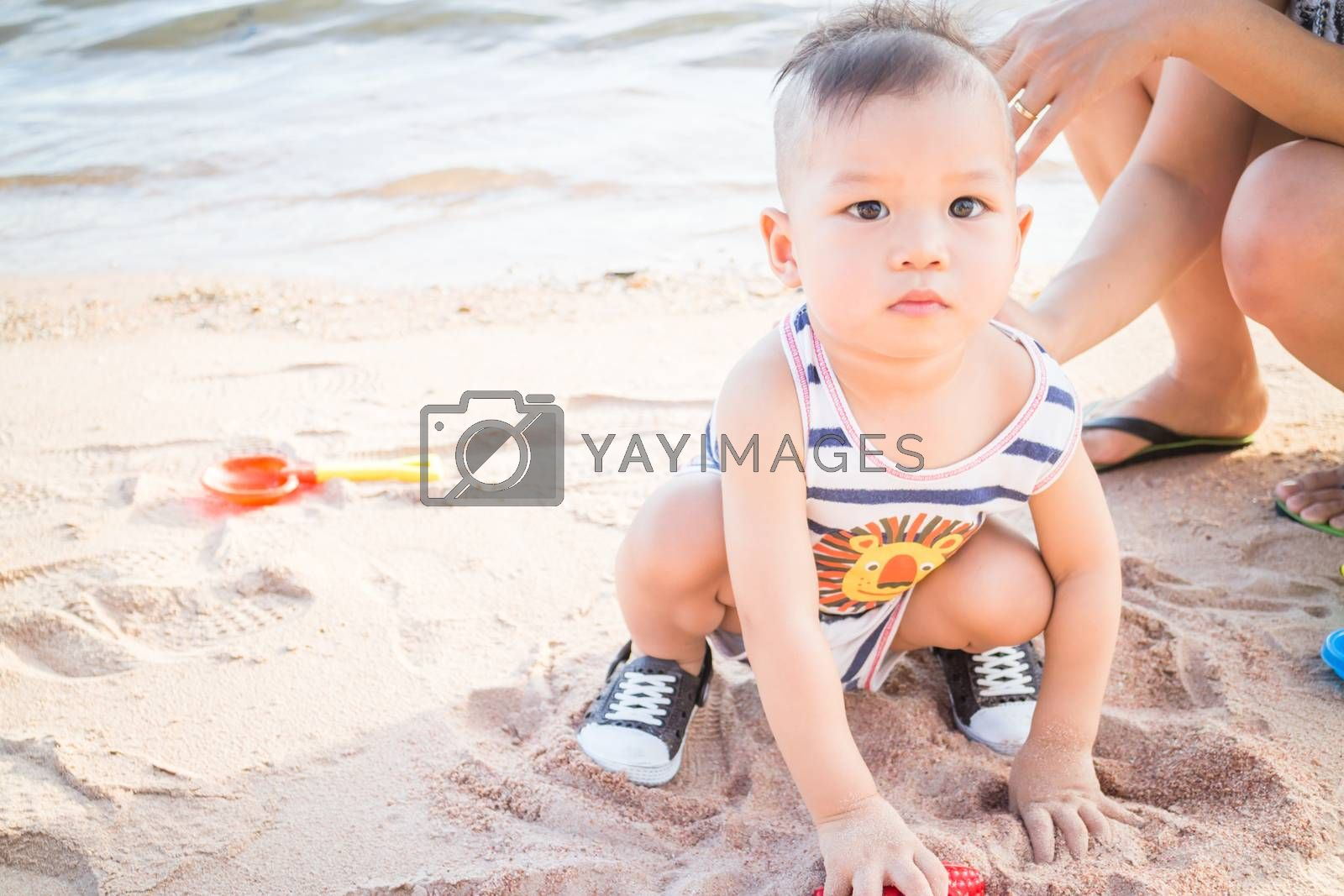 Little cute boy playing sand on the beach, stock photo