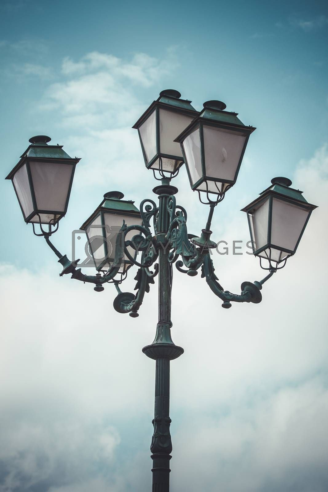 vertical, traditional street lamp with decorative metal flourishes