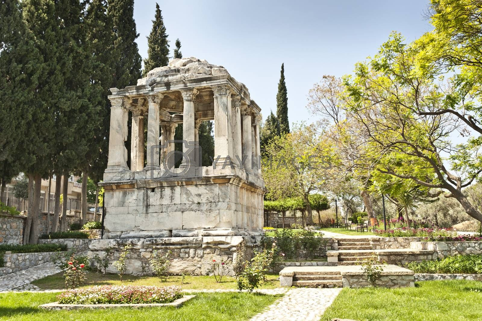 """The Mausoleum lies in the Street of  gumuskesen and is well known for being a Roman version of the Halikarnassos Mausoleion, which was recognized as one of the seven wonders of the ancient era. Since the Mausoleum was constructed on the most attractive site in the Roman Necropolis, there was a principle that forced the owner of the building to be an important person for the city. Namely, the owner of this place was expected to be a noble man, a manager or a person recognized as the member of a royal family. This mausoleum, being an exemplary construction thanks to the embellishing stonemasonry and the plan schedule, was constructed in the 2nd century AD, when the Antonins were ruling over Rome. The mausoleum consists of three divisions: (1) the ground floor that serves as a funerary chamber, (2) the second floor that represents the peristillium and the (3) pyramidal top floor. The walls of the ground floor consist of perfectly caved large marble blocks. The coating style of the gate in this construction is based on the same coating technique that was used for the Baltali Gate. The roof of the mausoleum was enriched from one end until the other thanks to relief plants and flowers and geometric motives. People make effort so that the gumuskesen Mausoleum, which represents the Roman Period, takes its place in the """"Word Heritage List"""" that has been prepared by UNESCO."""