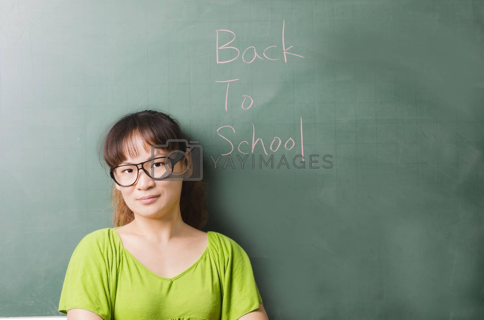 Royalty free image of Beauty teacher standing next to a blackboard by FrankyLiu