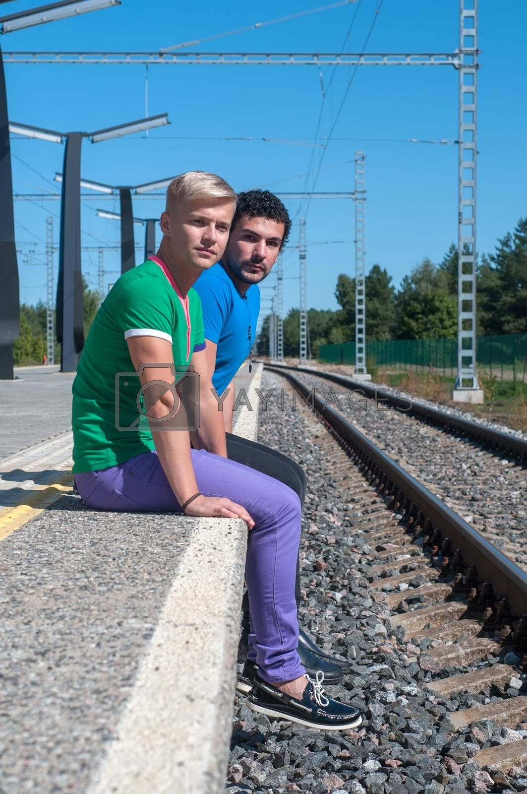 Two young trendy men sitting on the platform