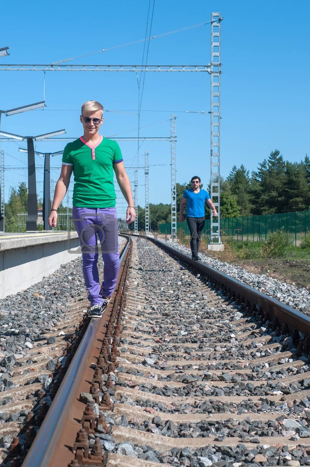 Two young men walking on the rail track by anytka