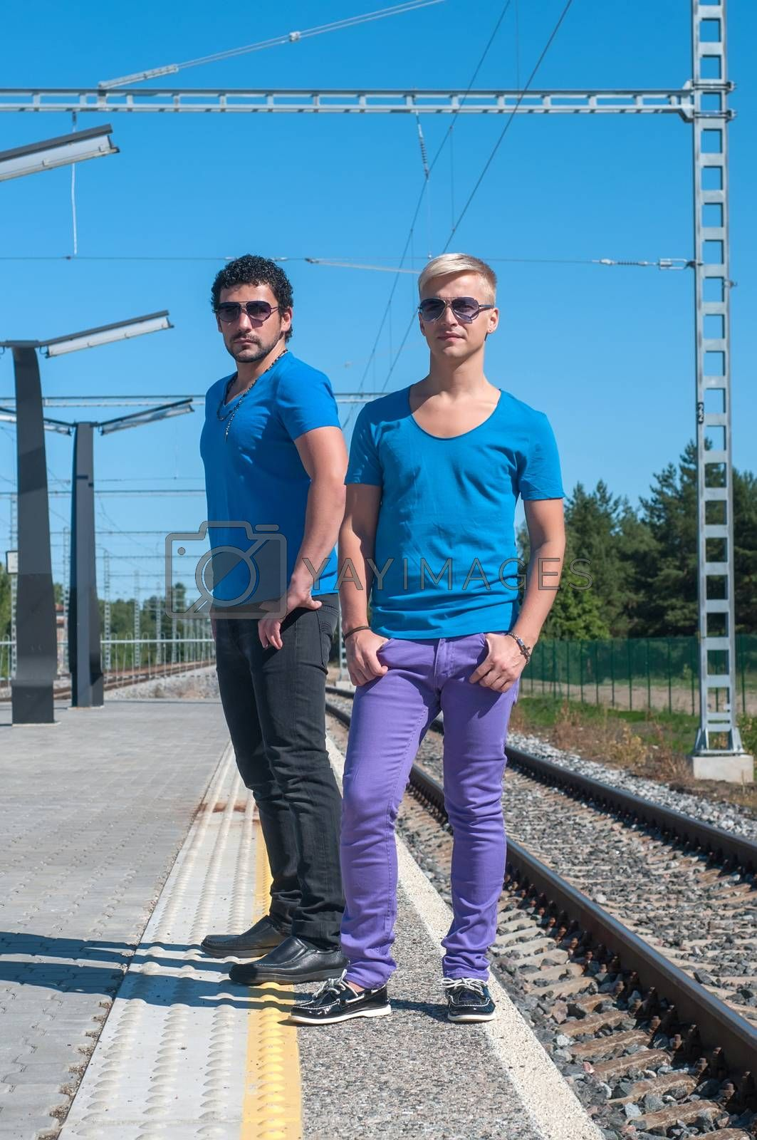 Two young trendy men standing on the platform
