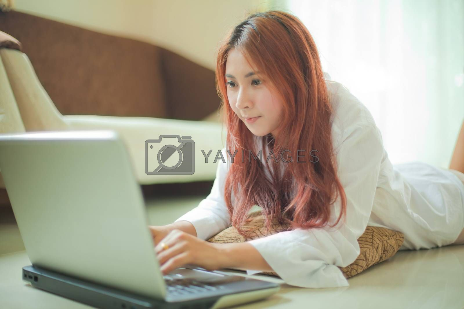 Young asian woman lying and using a laptop in home