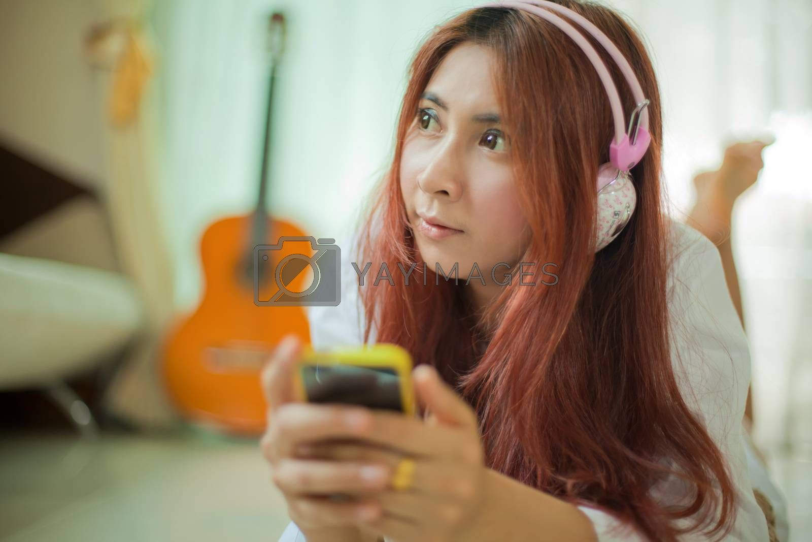 Young asian beautiful woman with smart phone and listening to music at home