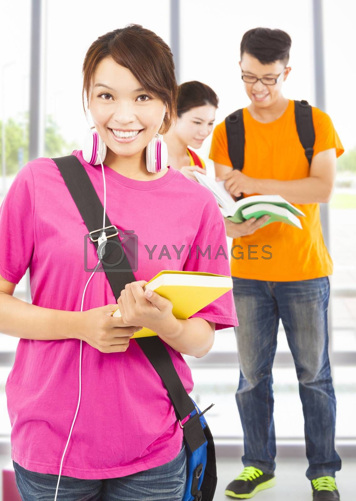 Royalty free image of pretty young student holding books and earphone with classmates by tomwang