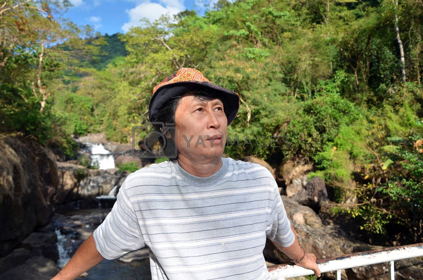 Senior man enjoying the nature with beautiful waterfall in background
