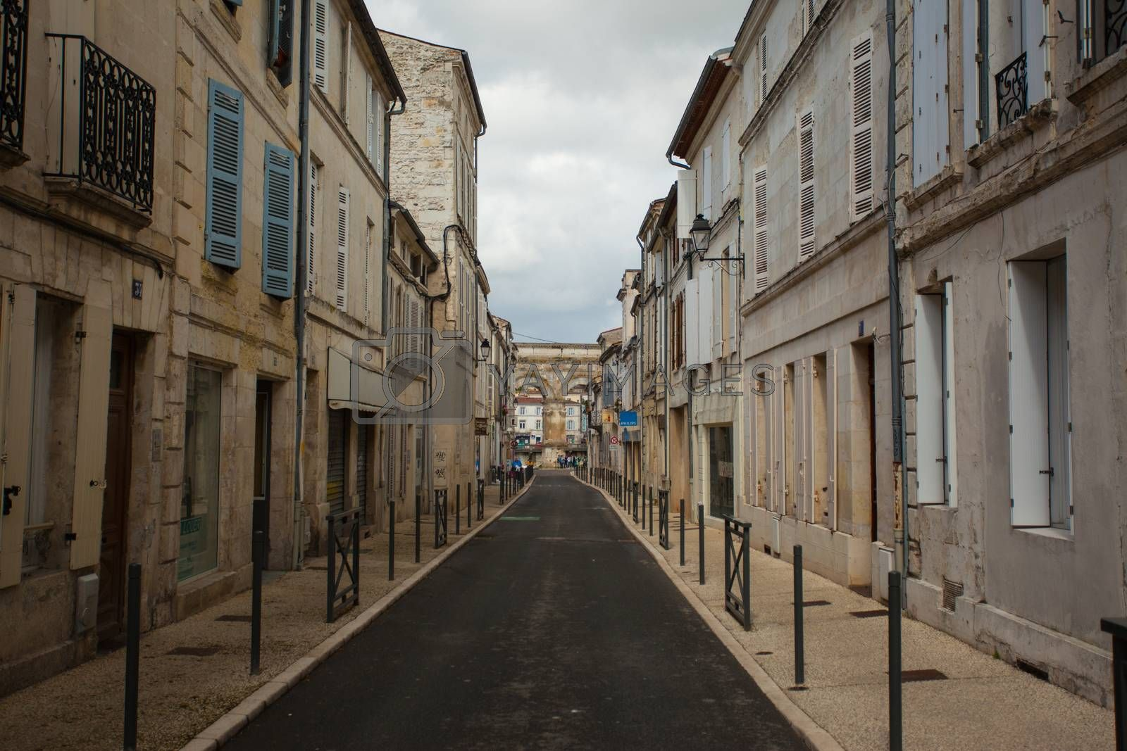 Typical street in Saintes with ist Germanic roman arch at the bottom, Charente,France