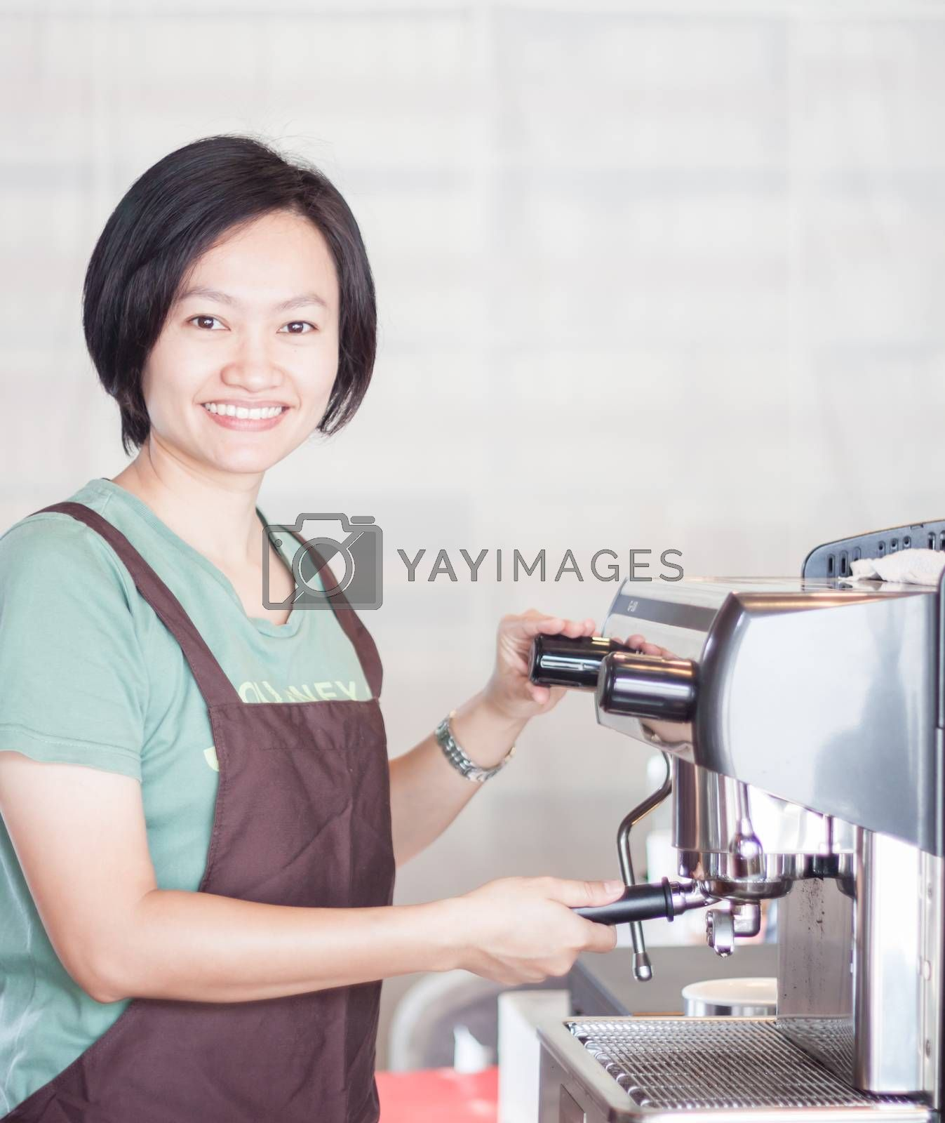 Woman barista at work in coffee shop, stock photo