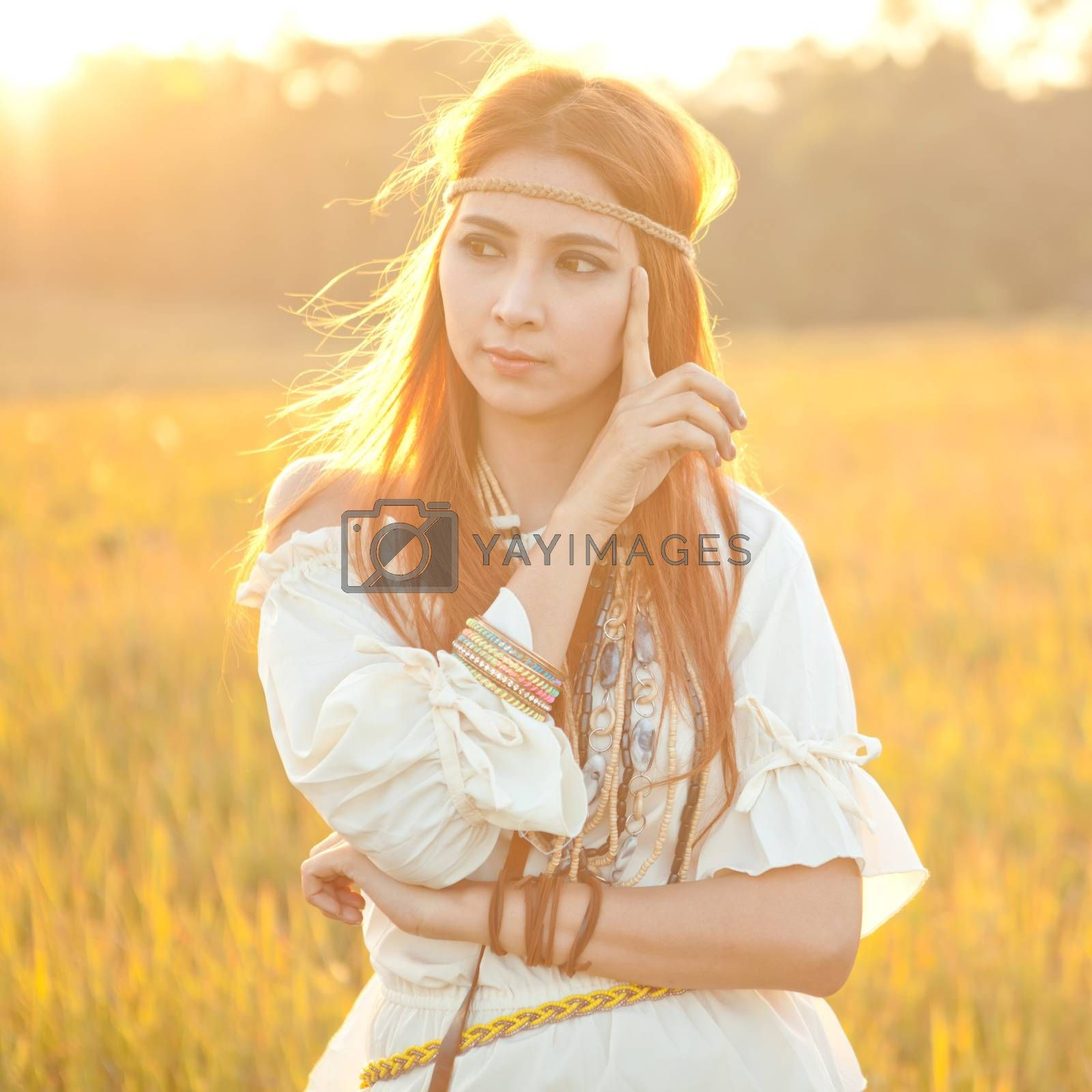 Hippie woman posing in golden field on sunset
