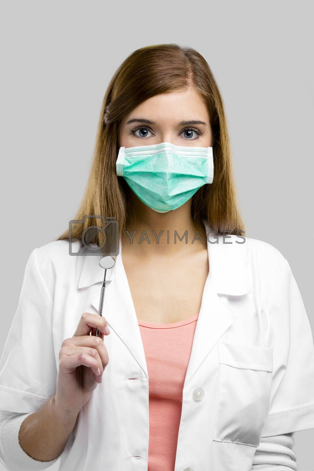 Beautiful and attractive female dentist with tools, isolated over a white background