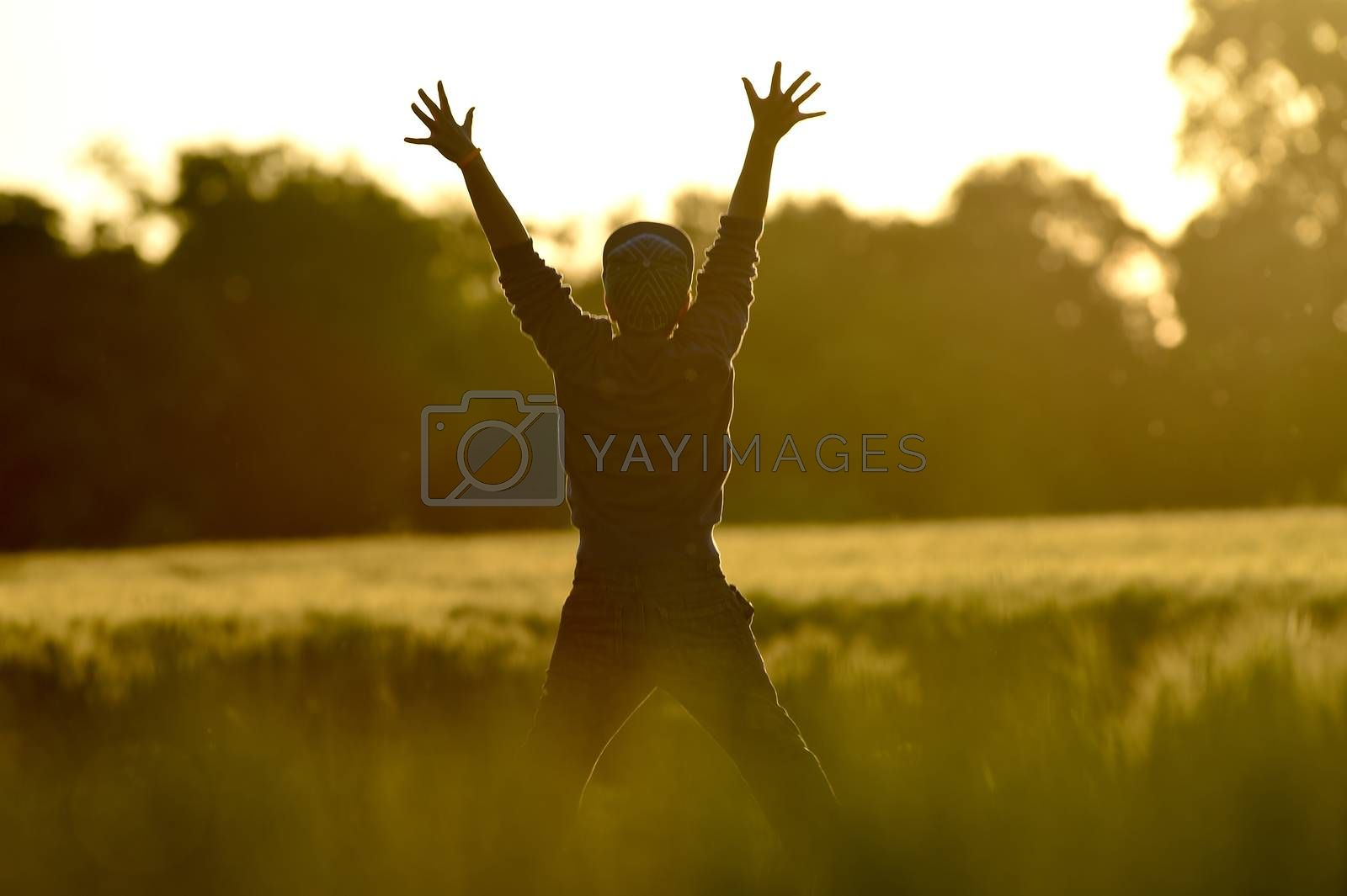 Little Boy Freedom jumping in wheat field at sunset