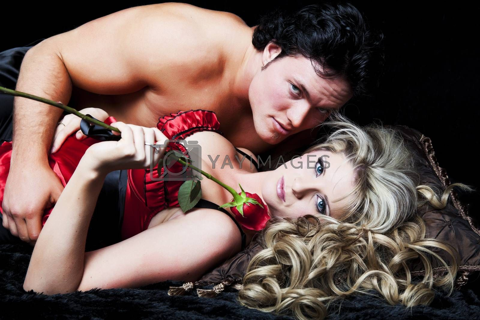Romantic couple in lingerie with red rose on black background.