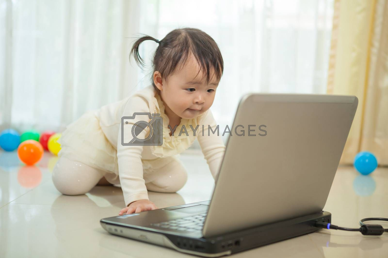 Little asian girl play laptop in home by witthaya
