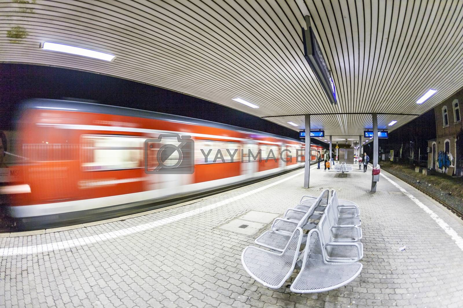ESCHBON, GERMANY - MARCH 18, 2010: people wait for arriving train Line S3 at train station in Eschborn, Germany. Frankfurt public transport system is operated by the company RMV. S3 serves the area Frankfurt to Bad Soden.