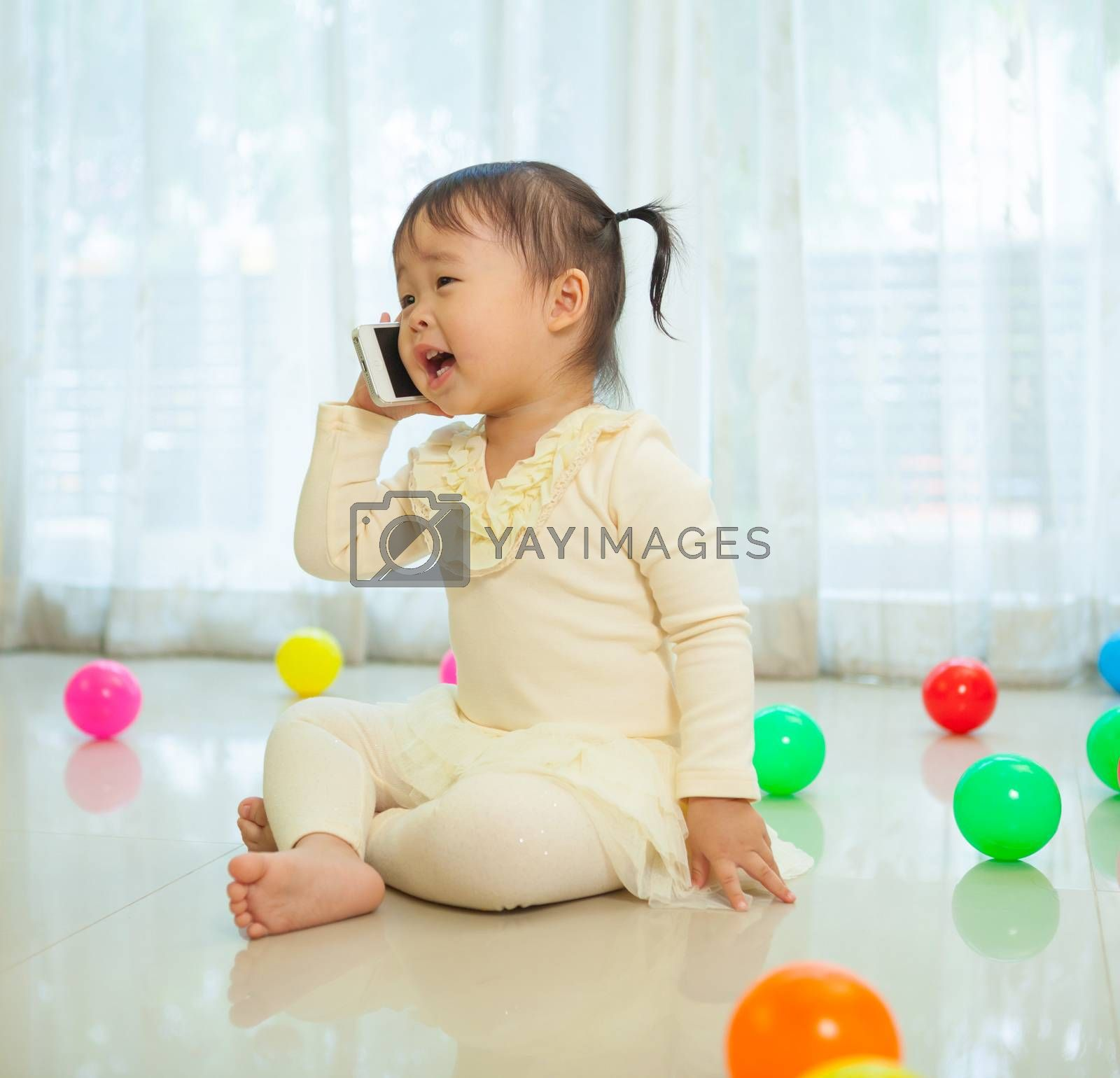 Little girl talking on mobile phone by witthaya