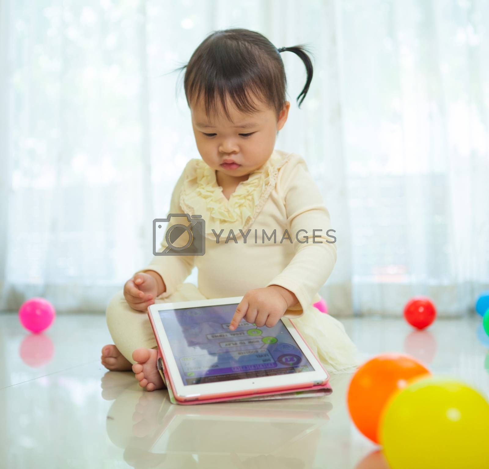 Happy little asian girl using tablet in the home