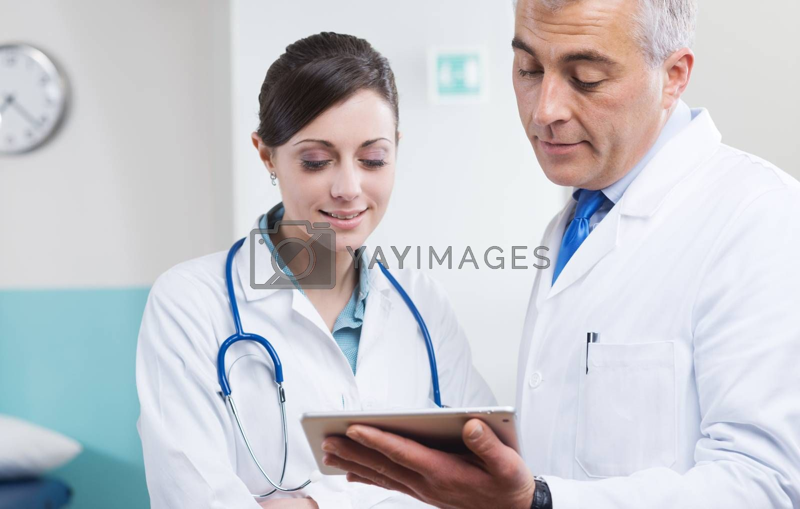 Doctors at hospital working together with a digital tablet.