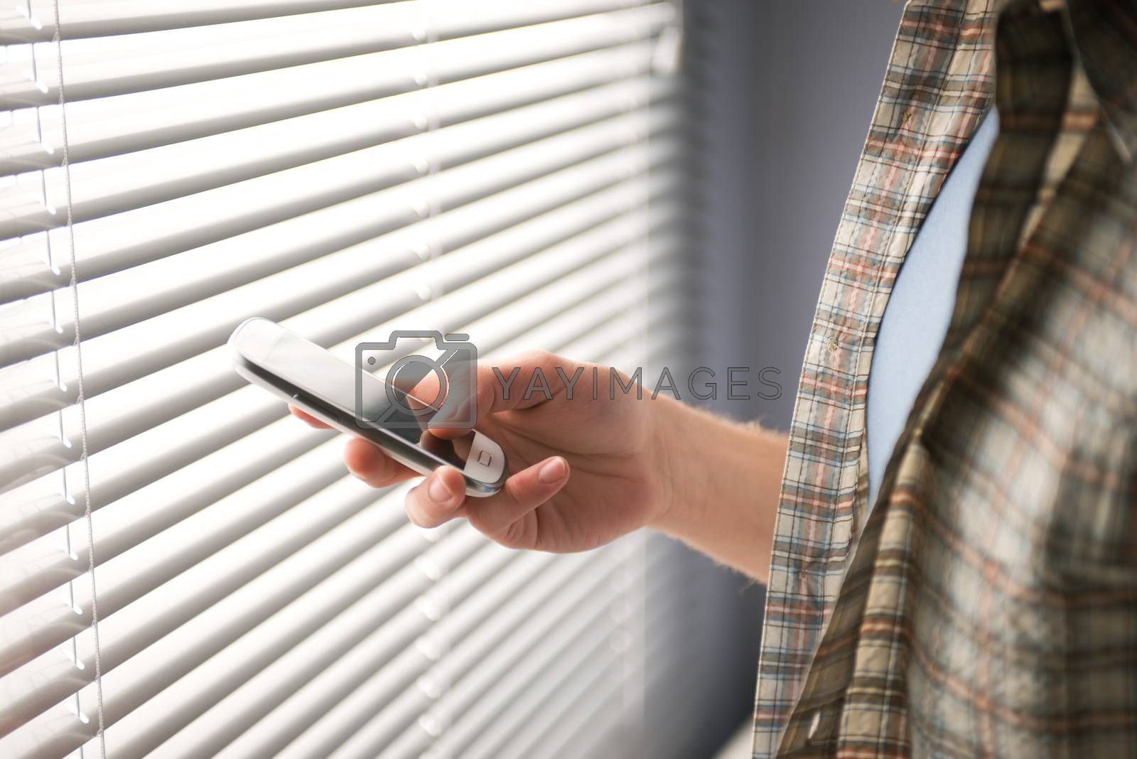 Young man using a smartphone in front of a window.