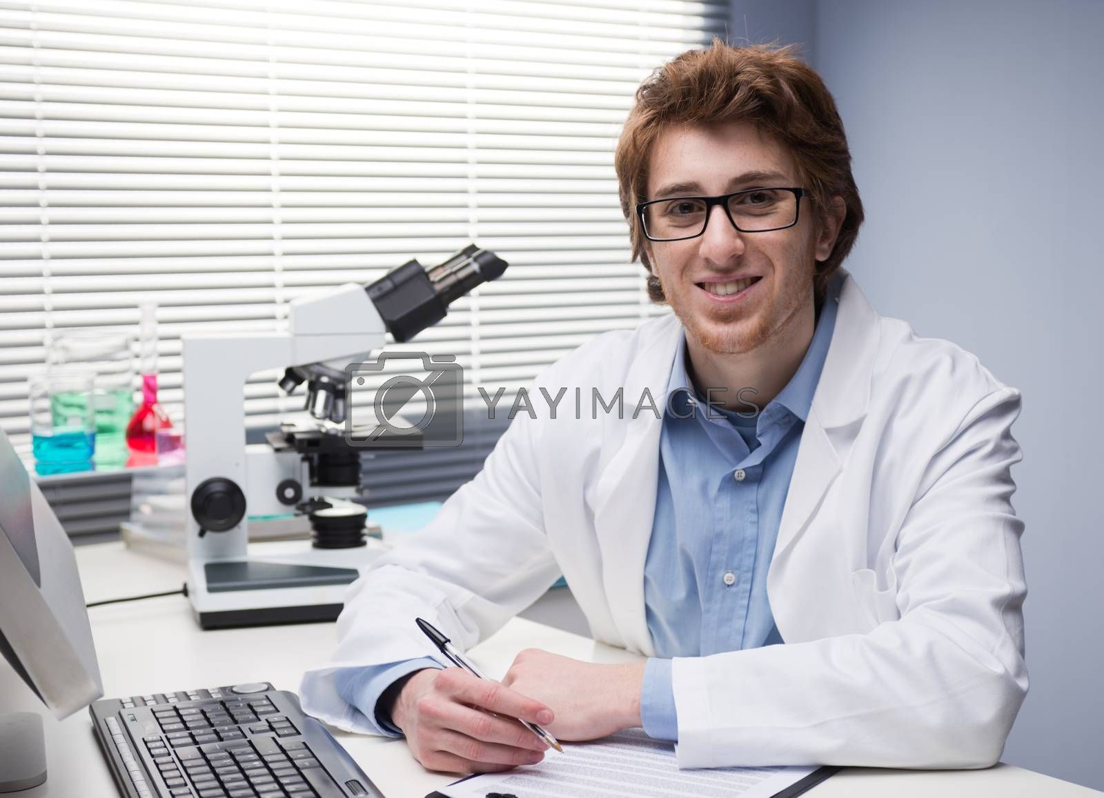 Young researcher writing notes at desk in the chemical lab.