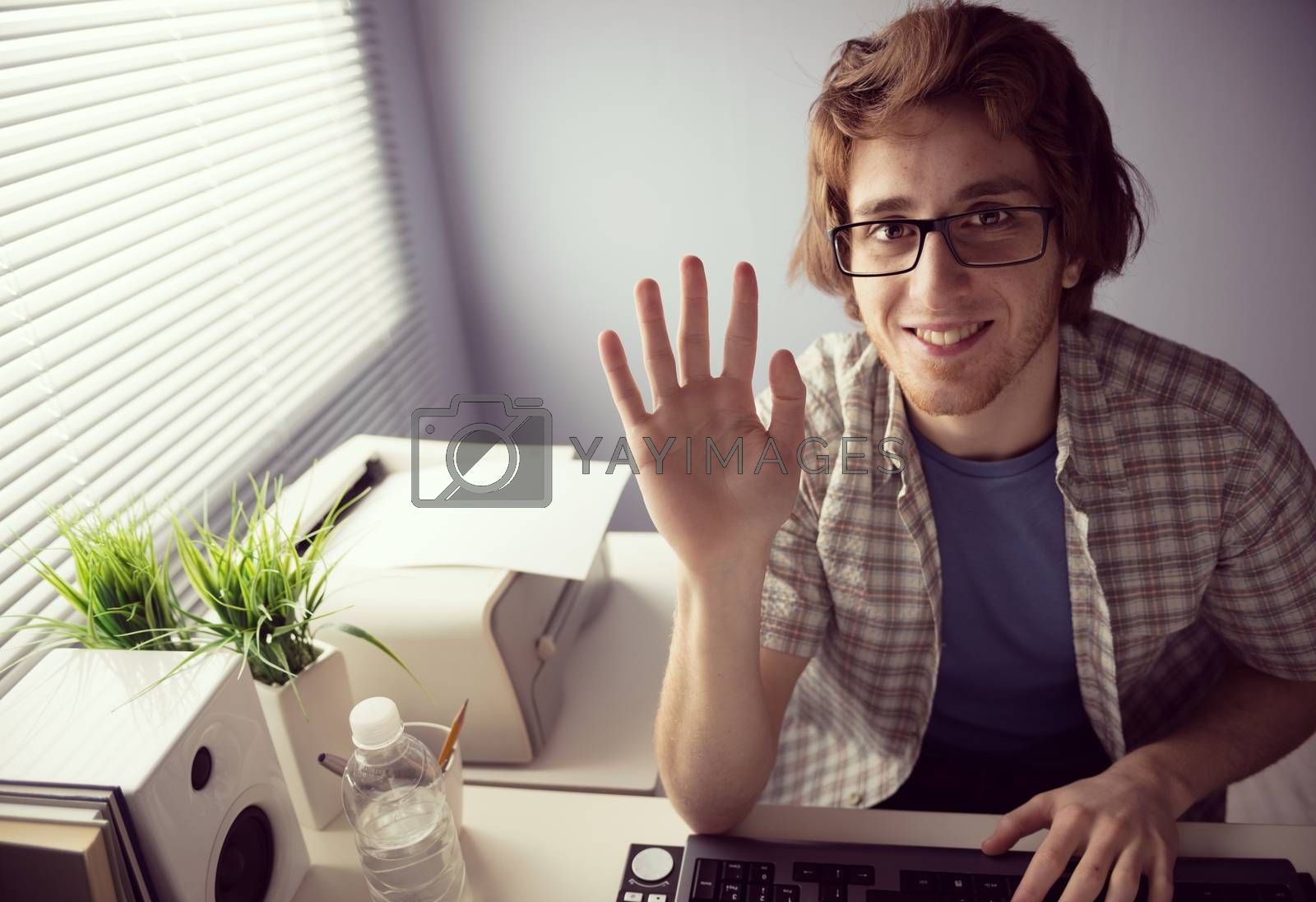 Young friendly guy smiling on web cam and waving hand.