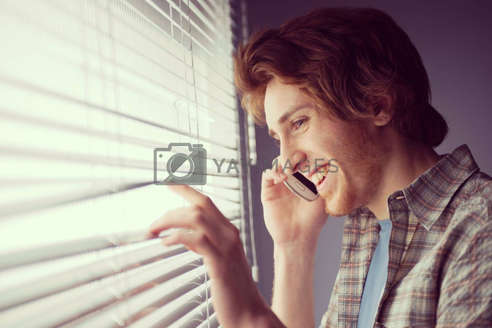 Young man smiling and talking on the phone in front of a window.
