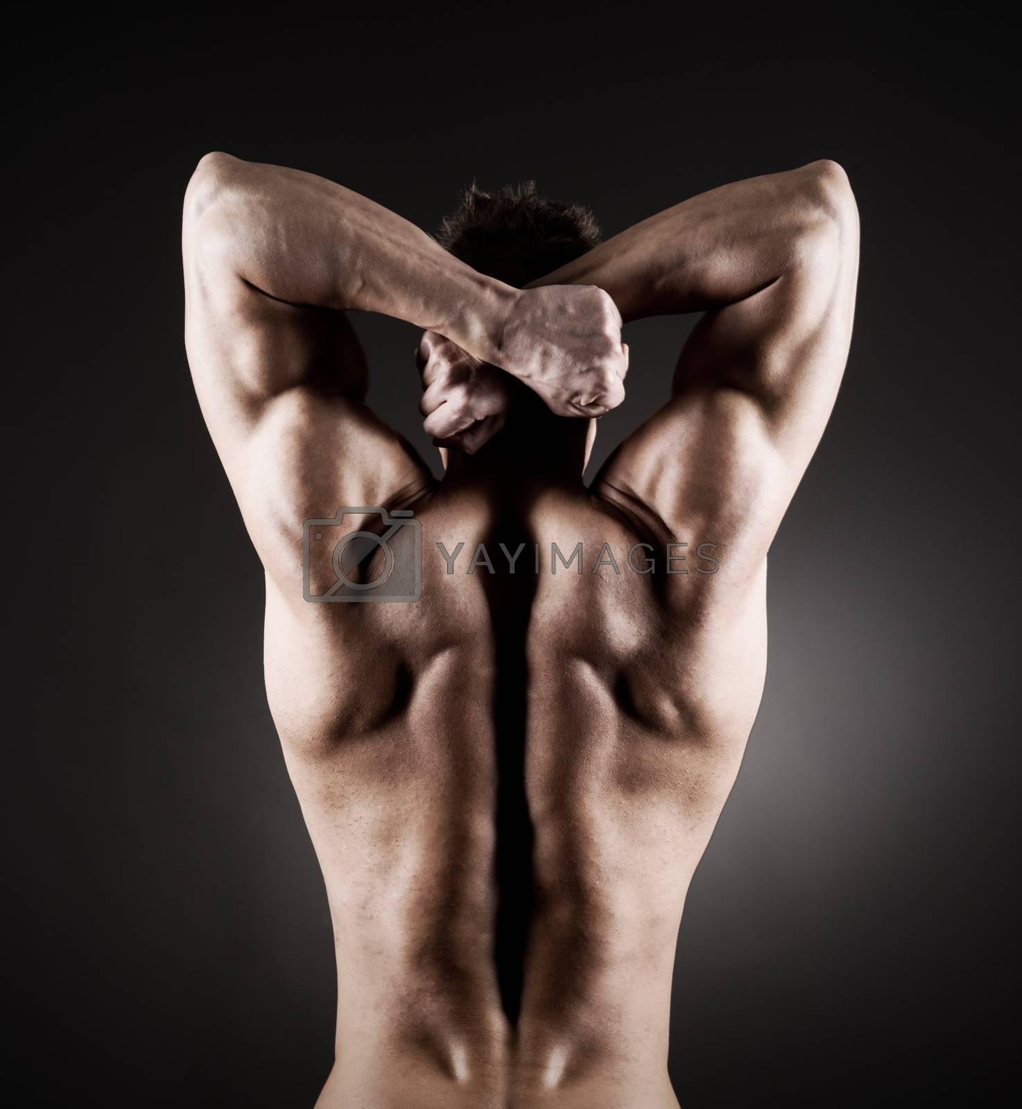 Body builder posing on dark background, rear view.