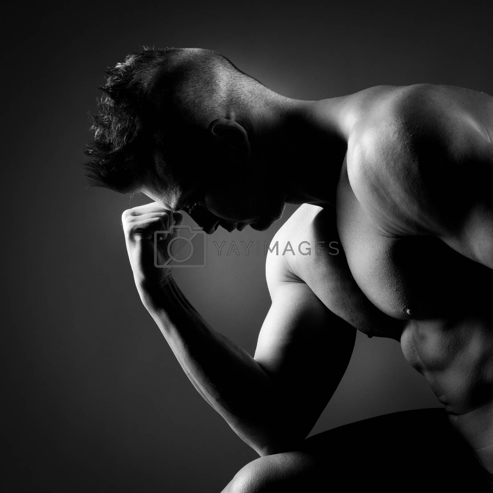 Attractive body builder posing and showing off muscles on dark background.