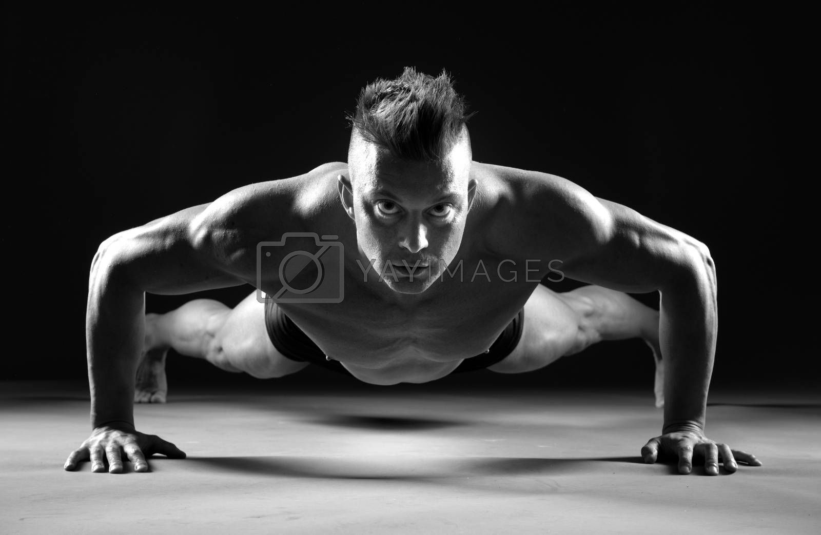 Muscular man doing push-ups  and looking forward on dark background.