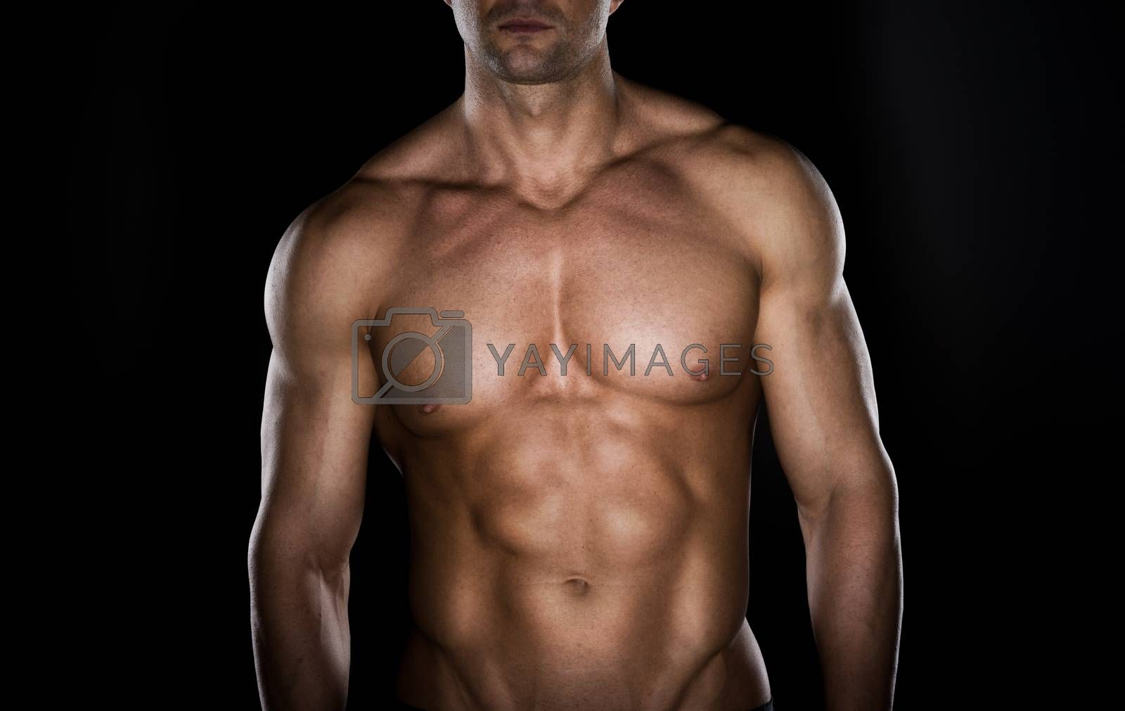 Bare chested muscular man looking down on dark background.