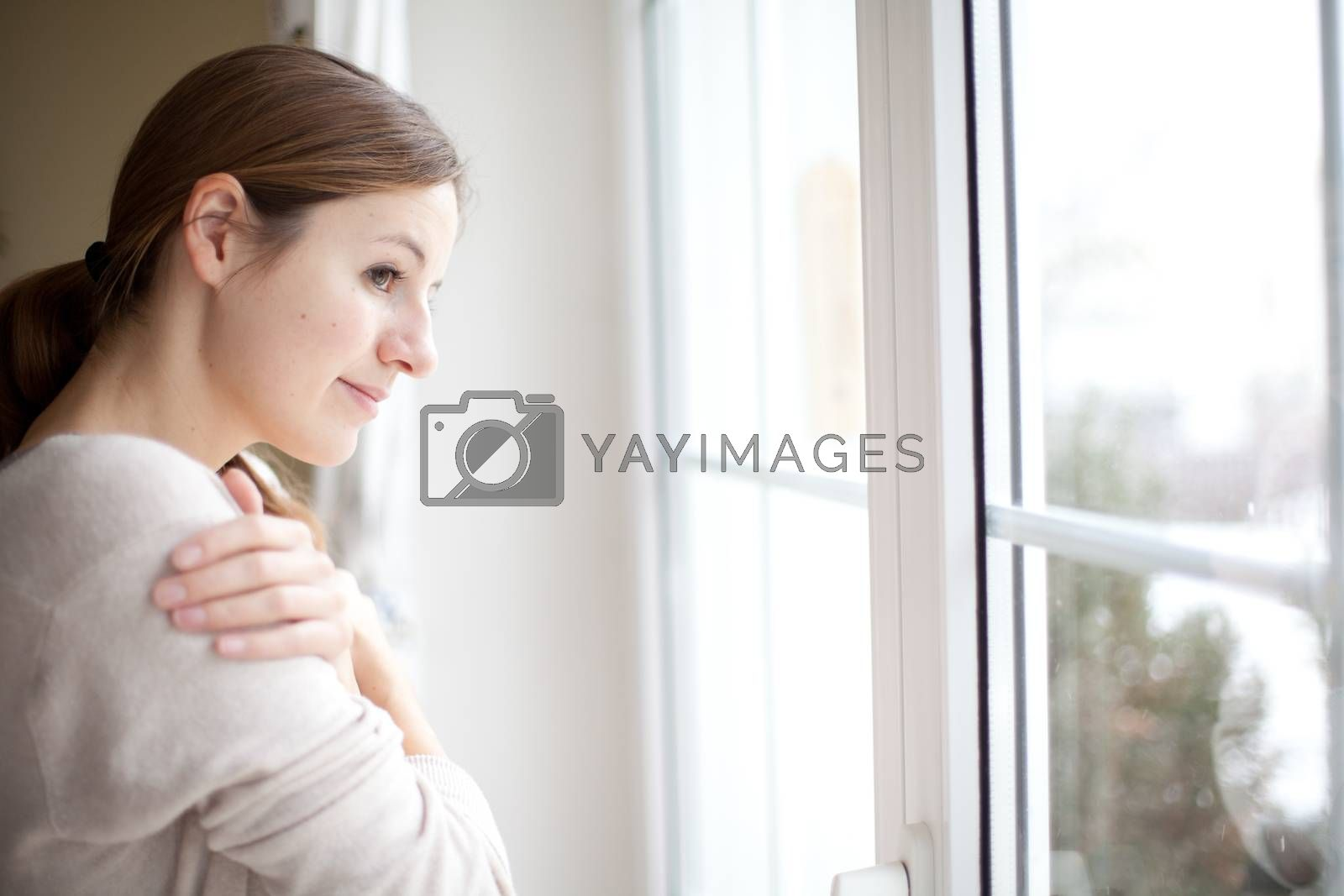 Woman lookong from a window of her house on a cold and snowy winter day