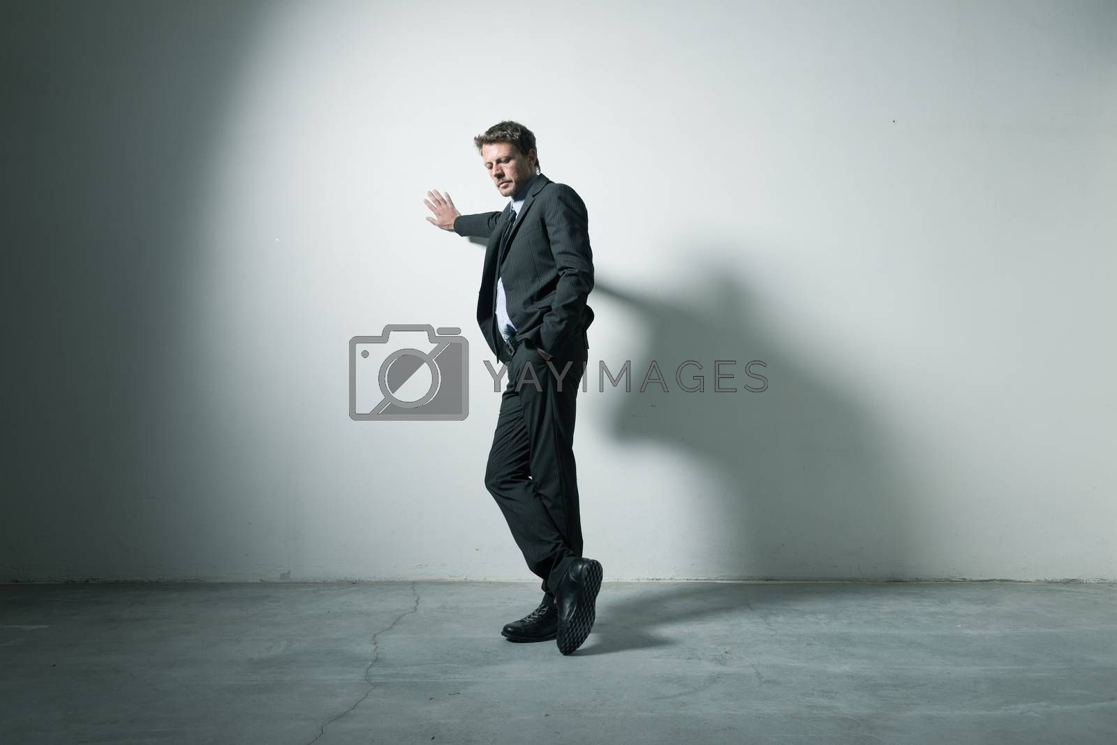 Tired pensive businessman leaning on a wall in an empty room with dramatic lighting.