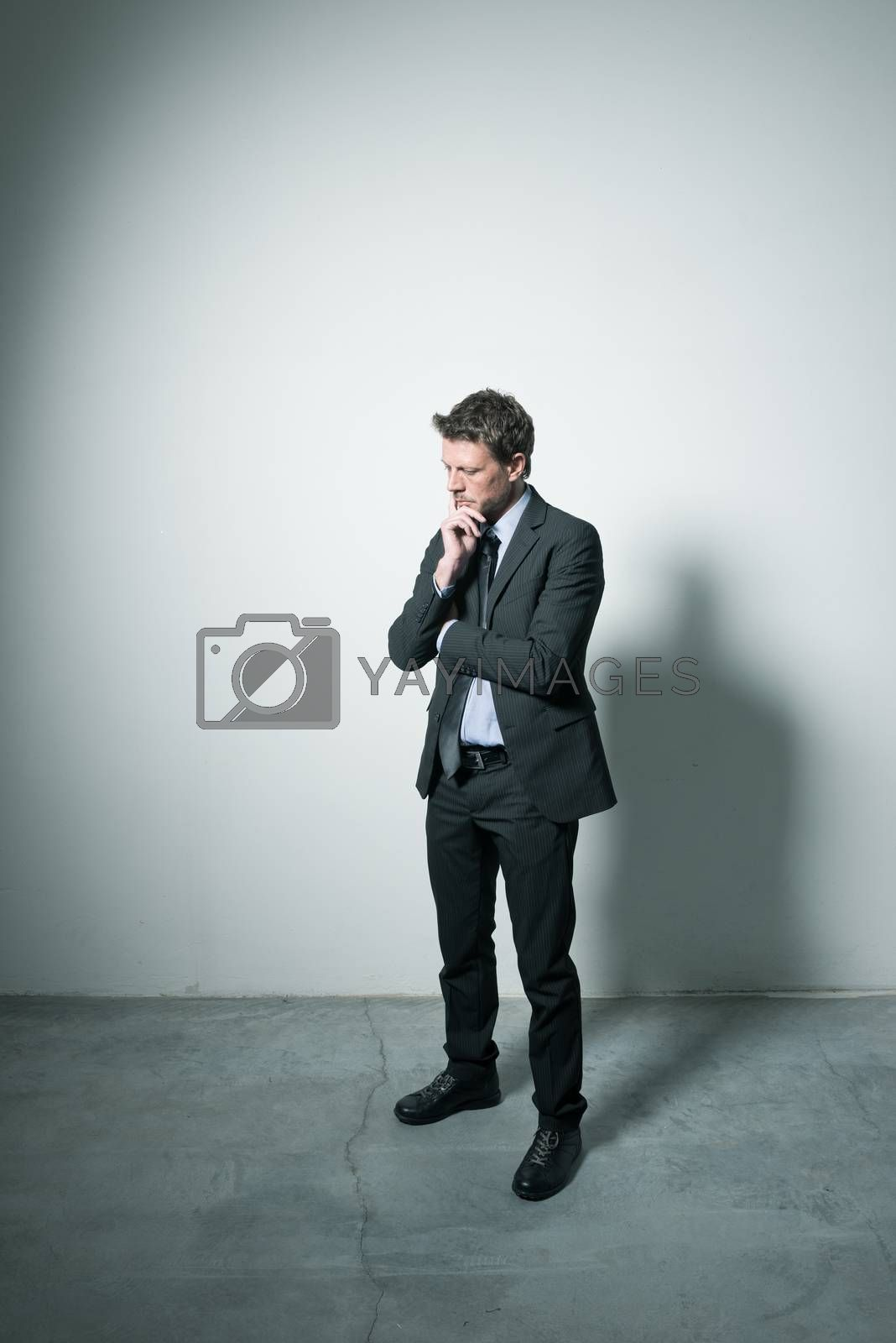 Businessman standing with hand on chin in a dark empty room.