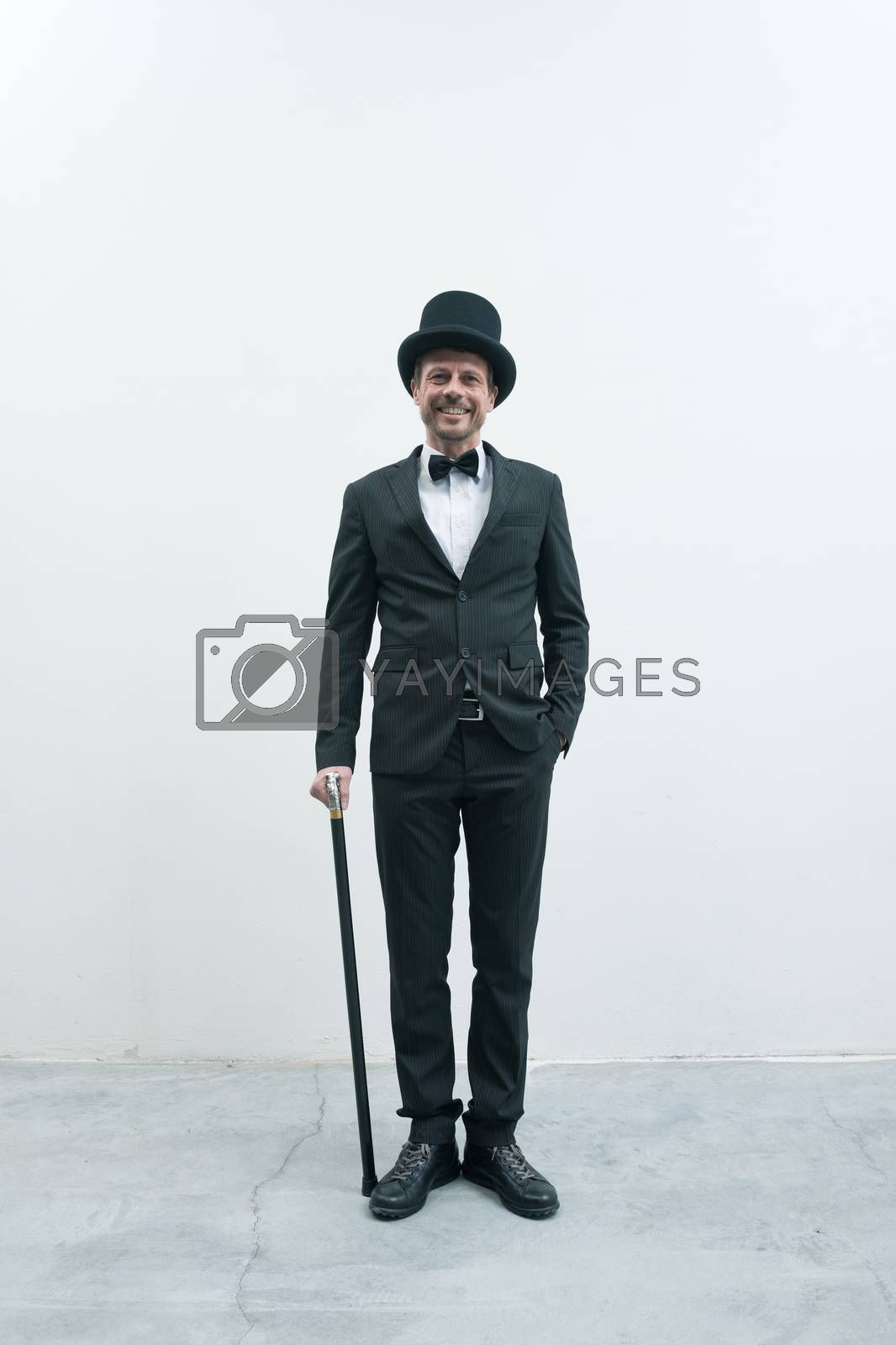 Classy smiling gentleman standing on white background and concrete floor in elegant suit with cane and bowler hat.