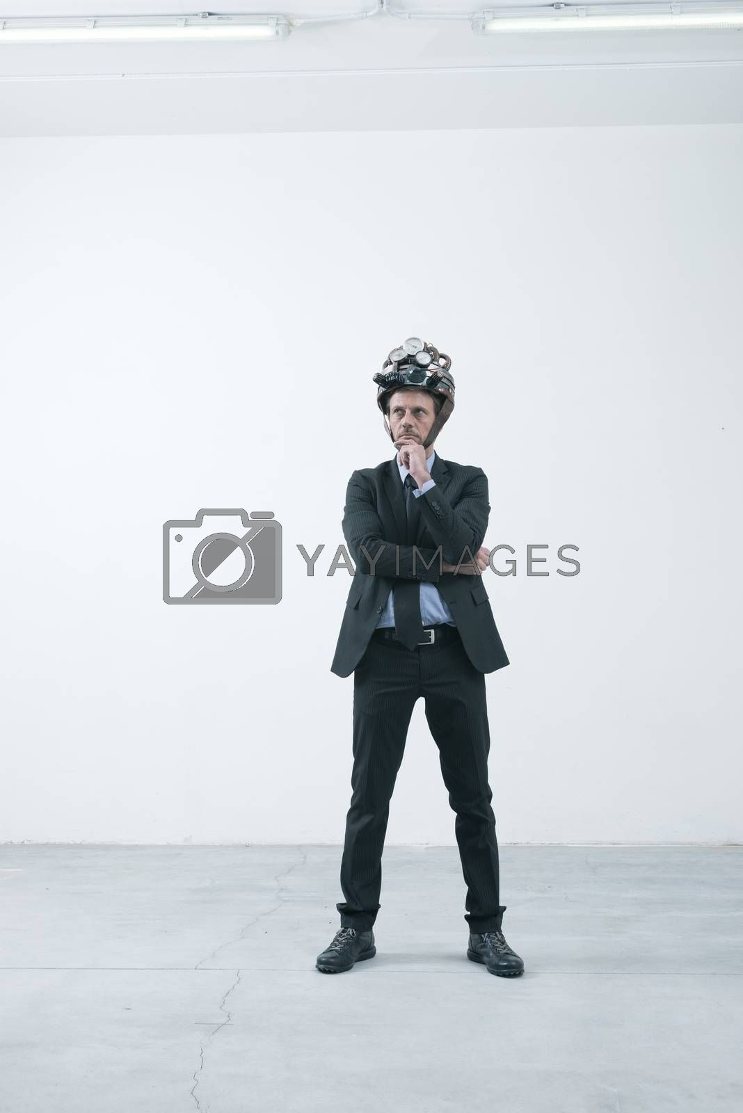 Confident businessman thinking with hand on chin wearing steampunk helmet