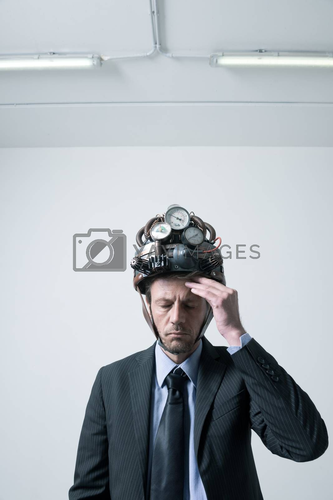 Tired pensive businessman touching his forehead weaaring futuristic helmet with gauges.