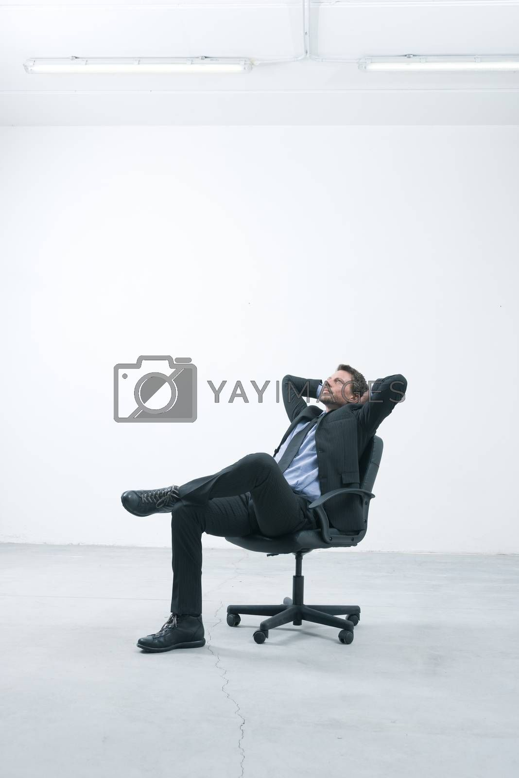 Thinkful businessman sitting on office chair with hands behind head in his new empty office.