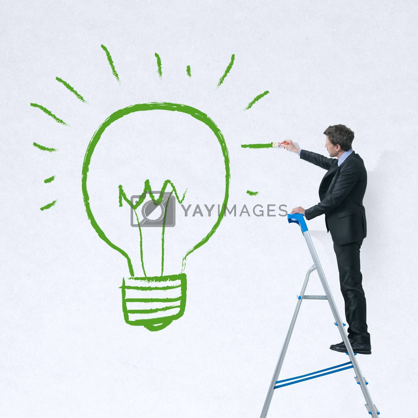 Businessman on a ladder painting a green lit bulb on a white wall.