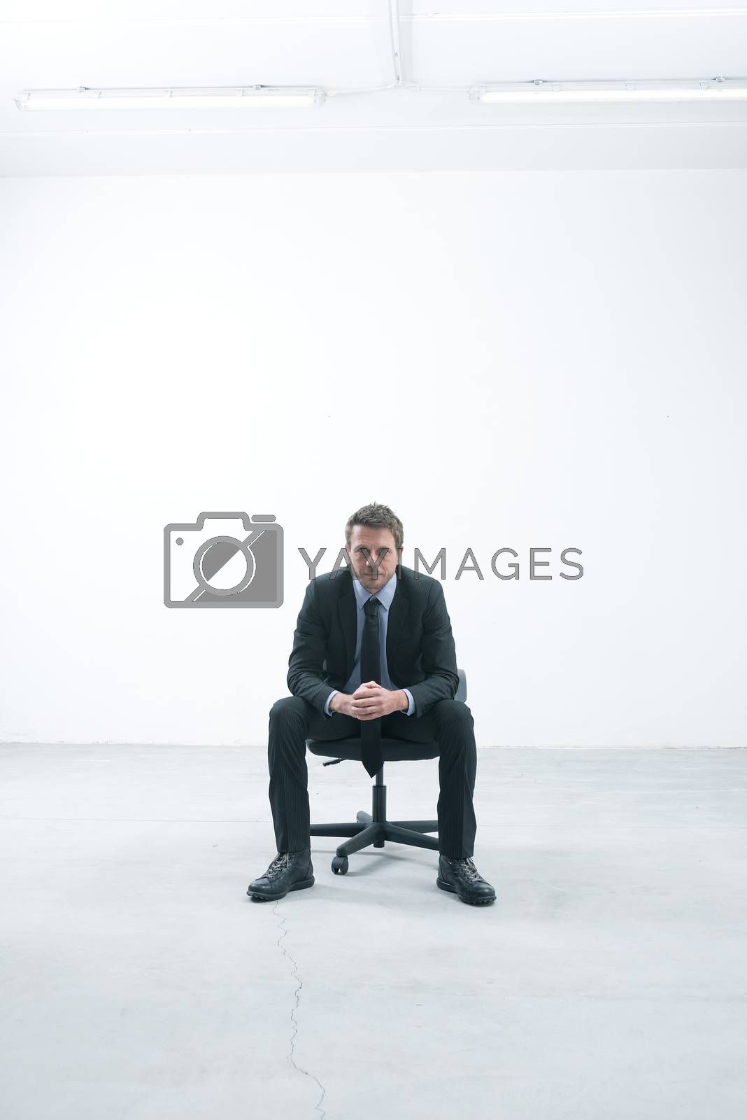 Elegant businessman sitting on an office chair in an empty room looking at camera.