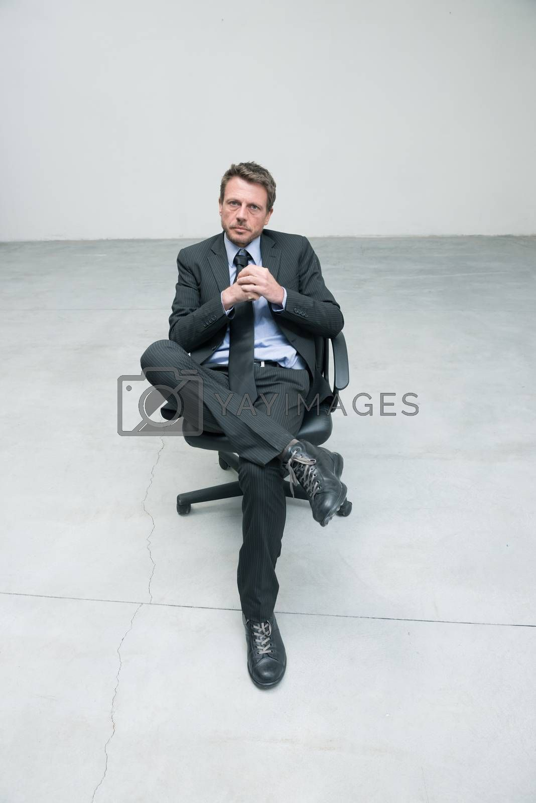 Businessman sitting on an office chair against concrete floor background.